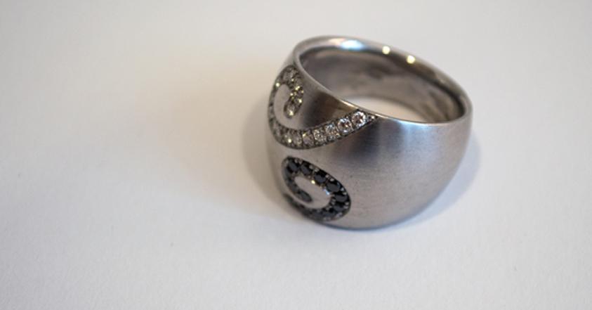 Großer Silberring mit Ornamenten aus weißen und schwarzen Diamanten.